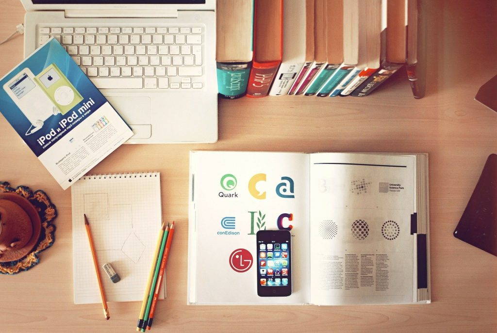 aerial view of laptop, books, pencils and cell phone