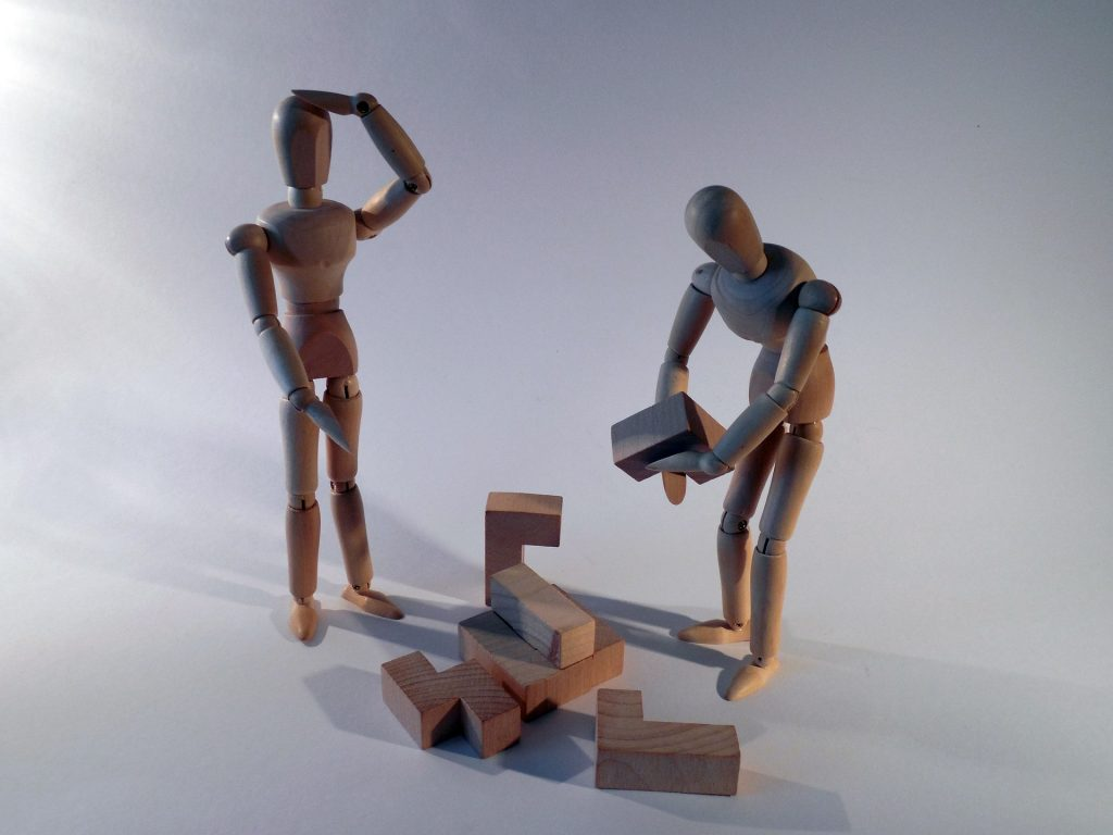 wooden figures working on a puzzle together